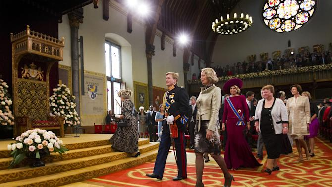 """Dutch Queen Beatrix, at left, walking up the stairs, arrives together with Crown Prince Willem Alexander centre left, and his wife Princess Maxima, right, to formally open the new parliamentary year with a speech outlining the government's plans for its 2013 budget,  in The Hague, Netherlands, Tuesday, Sept. 18, 2012. The Netherlands' Queen Beatrix underlined her country's commitment to the euro during her annual address to Parliament about the national budget on Tuesday, and made it clear the country will continue to pursue """"austerity"""" policies in response to Europe's debt crisis. (AP Photo/Vincent Jannink)"""