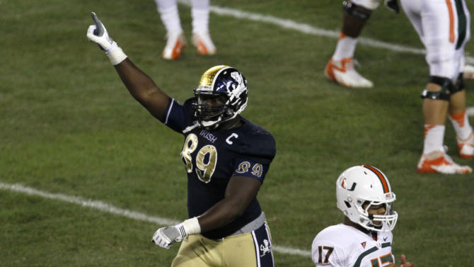 Notre Dame defensive end Kapron Lewis-Moore (89) celebrates after Miami quarterback Stephen Morris (17) was unable to convert on fourth down during the second half of an NCAA college football game at Soldier Field on Saturday, Oct. 6, 2012, in Chicago. Notre Dame won 41-3. (AP Photo/Charles Rex Arbogast)