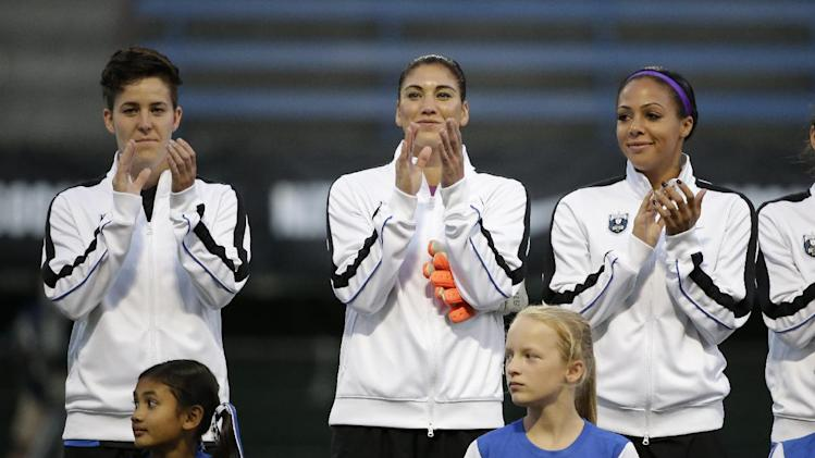 Seattle Reign FC's Keelin Winters, left, Hope Solo and Sydney Leroux applaud during introductions before an NWSL semifinal soccer match against the Washington Spirit' Sunday, Aug. 24, 2014, in Seattle. (AP Photo/Elaine Thompson)