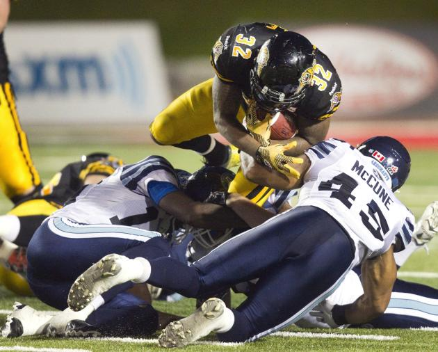 Tiger-Cats Gable dives over Argonauts McCune for a first down in the second half of their CFL game in Guelph