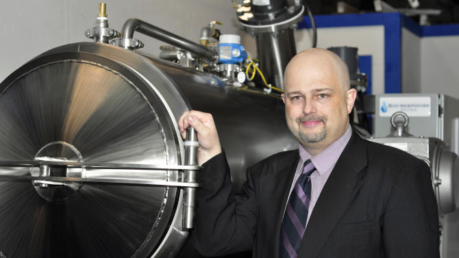 FILE- In this Feb. 14, 2011 photo provided by Edwards Funeral Home in Columbus, Ohio, Jeff Edwards stands next to an alkaline hydrolysis device that uses lye and heat to dissolve a body as an alternative to burial or cremation. The Ohio funeral home was blocked from dissolving bodies using lye and heat and announced Sunday, April 1, 2012, that it has joined a funeral directors' group in pushing for the state to legalize the process. Edwards was the first U.S. funeral business known to publicly offer alkaline hydrolysis and used the method in 19 cases before the state Board of Embalmers and Funeral Directors and the Ohio Department of Health stepped in with permit restrictions that impeded use of the process. (AP Photo/Edwards Funeral Home, File)