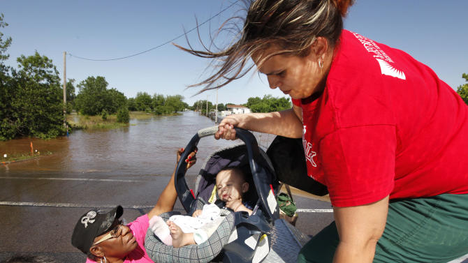 Riley Webb hands her seven month old baby Bryce Webb down to Oklahoma County Commissioner Willa Johnson after being rescued by Midwest City Fire Dept. personnel from a flooded mobile home park off of Air Depot Blvd. between NE 10th and NE 23rd St. in Midwest City, Okla, Saturday, June 1, 2013, after up to eight inches of rain fell during the previous 24 hours. (AP Photo/The Oklahoman, Paul Hellstern) LOCAL STATIONS OUT (KFOR, KOCO, KWTV, KOKH, KAUT OUT); LOCAL WEBSITES OUT; LOCAL PRINT OUT (EDMOND SUN OUT, OKLAHOMA GAZETTE OUT) TABLOIDS OUT