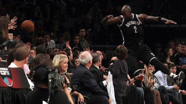 Brooklyn Nets power forward Kevin Garnett (2) dives into the crowd to try and save a ball going out of bounds against the Miami Heat (Reuters)