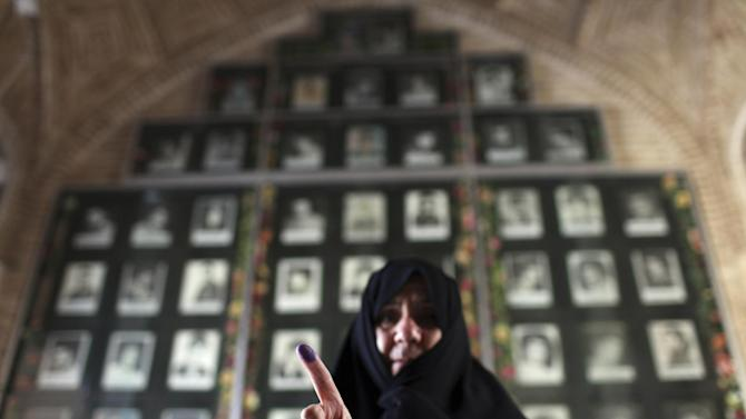 An Iranian woman displays her ink-stained finger after voting in the presidential and municipal council elections at a polling station in Qom, 78 miles (125 kilometers) south of the capital Tehran, Iran, Friday, June 14, 2013. Iran's supreme leader delivered a salty rebuke to the U.S. Friday as Iranians lined up to vote in a presidential election that has suddenly become a showdown across the Islamic Republic's political divide: hard-liners looking to cement their control and re-energized reformists backing the lone moderate. (AP Photo/Ebrahim Noroozi)