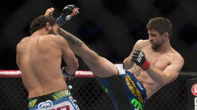 Carlos Condit, right, lands a kick to Johny Hendricks  during their UFC 158 welterweight fight in Montreal, Saturday, March 16, 2013. (AP Photo/The Canadian Press, Graham Hughes)
