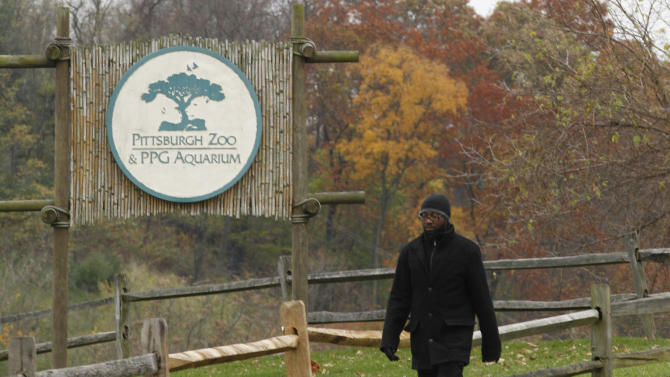 A man walks by a sign near the entrance to the parking lots for the Pittsburgh Zoo and PPG Aquarium on Monday, Nov. 5, 2012, in Pittsburgh. Zoo officials said a young boy was killed after he fell into the exhibit that was home to a pack of African painted dogs, who pounced on the boy and mauled him on Sunday, Nov. 4, 2012. It's not yet clear whether the boy died from the fall or the attack, said Barbara Baker, president of the Pittsburgh Zoo & PPG Aquarium. (AP Photo/Keith Srakocic)
