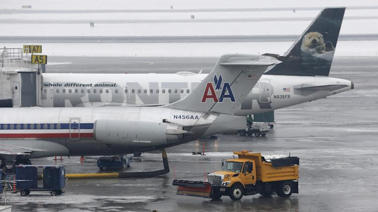 A truck with a plow drives pass an American Airlines and Frontier plane docked at their gates at the Salt Lake City Airport Thursday, Jan. 24, 2013. The Salt Lake City International Airport was closed due to icy conditions. A Frontier airplane slid on the runway during landing Thursday morning, but nobody was injured. Five flights were canceled and 15 other planes were forced to return to their gates when the runway was closed. The airport is a hub for Delta Airlines. Freezing rain has also caused dozens of accidents on roadways around Salt Lake City this morning.  (AP Photo/Rick Bowmer)