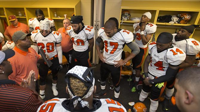 ADVANCE FOR WEEKEND EDITIONS, MAY 30-31 -  In this photo from May 16, 2015, Omaha Beef coach Cory Ross, at left holding folded papers, addresses his players in the locker room prior to playing the Sioux City Bandits in a Champions Indoor Football league game in Sioux City, Iowa. The players are an eclectic mix of dreamers hoping to get noticed by a team in the Arena Football League, CFL or even the NFL and realists who know they're going nowhere but still have fun playing. (AP Photo/Nati Harnik)