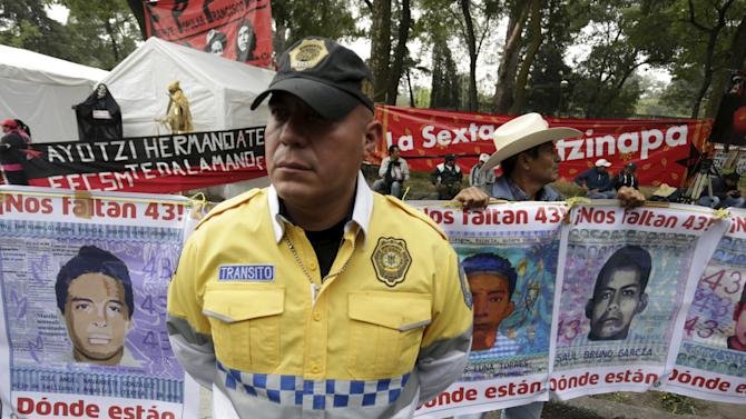 A traffic police officer stands guard next to demonstrators holding banners with pictures of missing students from the Ayotzinapa Teacher Training College Raul Isidro Burgos during a protest to demand justice for 43 students,in Mexico City