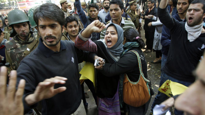 FILE - In this Feb. 9, 2013 file photo, an anti-death penalty activist tries to break up an altercation between right-wing Hindu nationalist Bajrang Dal activists, on left unseen, and Kashmiri students protesting the execution of Kashmiri Mohammad Afzal Guru, in New Delhi, India. For 11 years the family of the convicted terrorist waited and wondered about his fate as he sat on death row. Two weeks ago they found out — from television. Guru had been hanged in secrecy in a faraway jail in New Delhi. A government letter informing them of the imminent hanging arrived at their home in Kashmir two days after he was dead. (AP Photo/Tsering Topgyal, File)
