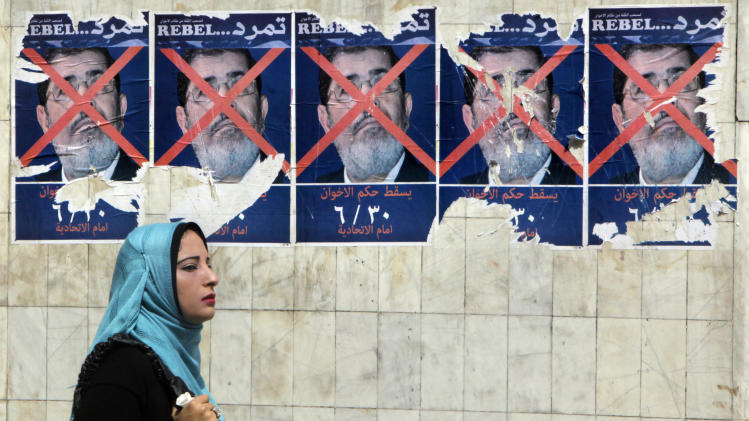 "An Egyptian walks past anti-government posters for a campaign calling for the ouster of Egyptian President Mohammed Morsi and for early presidential elections in Cairo, Egypt, Tuesday, June 11, 2013. Young activists are trying to rally public discontent with Egypt's Islamist President Morsi by fanning out in the streets and collecting millions of signatures on a petition calling for his removal. Morsi's Muslim Brotherhood has dismissed the campaign as irrelevant, even illegal, but the signature drive has stirred up Egypt's politics as the president nears the end of his tumultuous first year in office. The Arabic at the bottom of the poster reads, ""Down with the Muslim Brotherhood rule. June 30. At the presidential palace."" (AP Photo/Amr Nabil)"