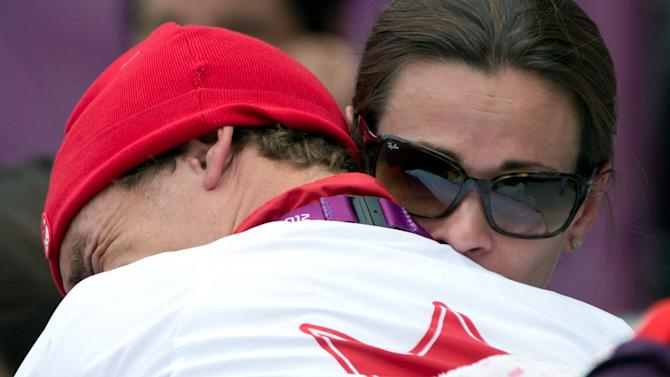 Simon Whitfield hugs his wife after crashing in the cycling portion of the men's triathlon at the London Olympics.