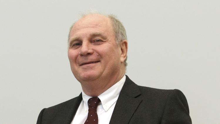 Bayern Munich President Hoeness smiles as he arrives for his trial for tax evasion at a regional court in Munich