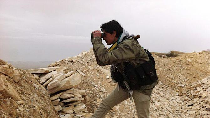 In this photo taken on Thursday, March 13, 2014, provided by the anti-government activist group Local Comity of Yabroud Town, which has been authenticated based on its contents and other AP reporting, a Syrian rebel looks through his binocular at one of the frontline of Yabroud town, the last rebel stronghold in Syria's mountainous Qalamoun region. Syria's uprising, which began with largely peace protests in March 2011, has evolved into a civil war with sectarian overtones. Islamic extremists, including foreign fighters and Syrian rebels who have taken up hard-line al-Qaida-style ideologies, have played an increasingly prominent role among fighters, dampening the West's support for the rebellion to overthrow Assad. (AP Photo/Local Comity of Yabroud Town)
