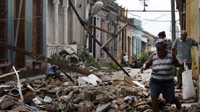 Residents walk through the rubble from homes that were damaged by Hurricane Sandy in Santiago de Cuba, Cuba, Friday Oct. 26, 2012.  Sandy was a Category 2 hurricane when it wreaked havoc in Cuba on Thursday, killing 11 people in eastern Santiago and Guantanamo provinces as its winds and rain destroyed thousands of houses and ripped off roofs.  (AP Photo/Franklin Reyes)