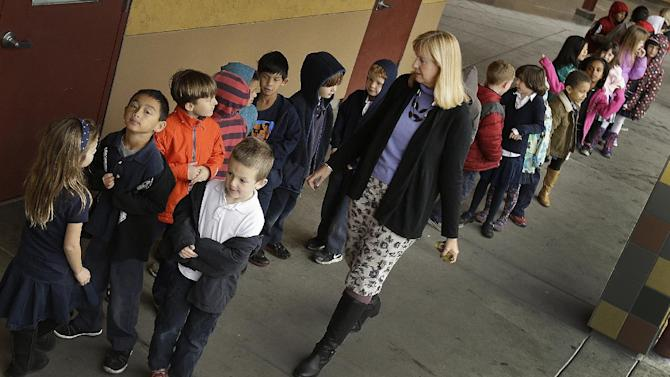 FILE - In this July 24, 2013 file photo, first grade teacher Lynda Jensen walks with her class of 30 children at Willow Glenn Elementary School in San Jose, Calif. The Common Core State Standards have been adopted by 45 states and the District of Columbia with the goal of making sure the nation's high school graduates leave school ready for college or a job. But despite their widespread adoption, many parents don't know what the standards are or whether their state has adopted them, according to an Associated Press-NORC Center for Public Affairs Research poll. (AP Photo/Ben Margot, File)