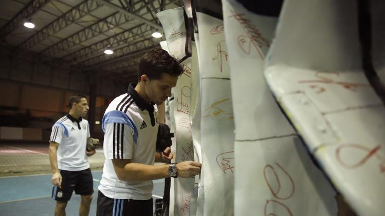 "Argentina's Gago and Rodriguez sign a sculpture by Swiss artist Pflugi called ""The Seeds of Victory"" in Rio de Janeiro"