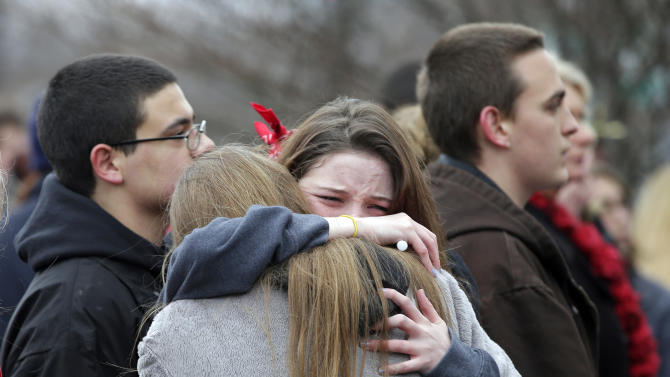 Two students hug at a memorial service in Chardon, Ohio Wednesday, Feb. 27, 2013 during a march to a memorial ceremony for three classmates who died in a school shooting rampage one year ago, Wednesday, Feb. 27, 2013. The march ended at the courthouse where 18-year-old shooter T.J. Lane pleaded guilty to all charges Tuesday. He could face life in prison at his sentencing March 19. (AP Photo/Mark Duncan)