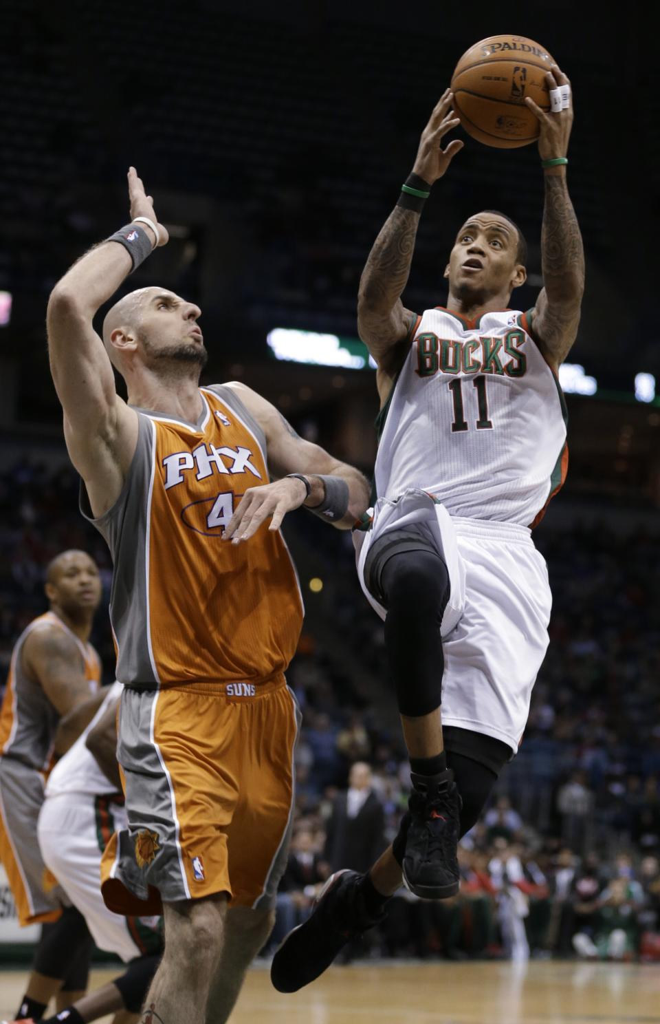 Milwaukee Bucks' Monta Ellis (11) drives against Phoenix Suns' Marcin Gortat (4) during the second half of an NBA basketball game Tuesday, Jan. 8, 2013, in Milwaukee. (AP Photo/Jeffrey Phelps)