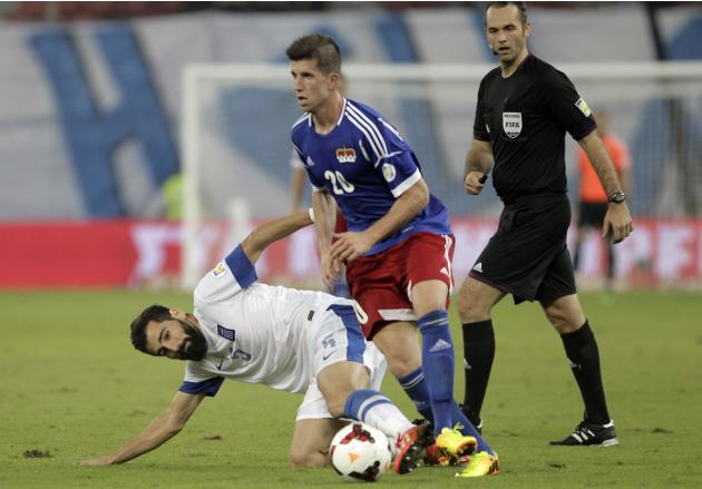 Greece's Siovas tackles Liechtenstein's Wieser during the 2014 World Cup qualifying soccer match in Piraeus near Athens