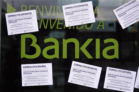 A man walks past a vandalized Bankia's bank office with papers stuck on it, in Barcelona