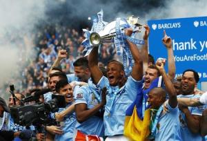 Manchester City's Kompany celebrates with the English Premier League trophy following their soccer match against West Ham United at the Etihad Stadium in Manchester