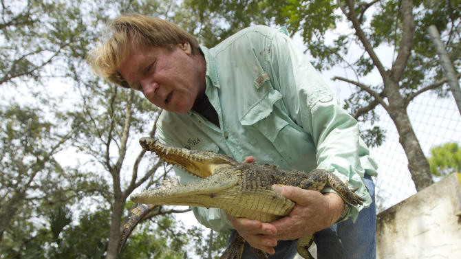 """In this Wednesday, Nov. 28, 2012 photo, Joe Wasilewski works with a captured Nile crocodile, caught near his Homestead, Fla., home. State wildlife officials have given their agents a rare order to shoot to kill in the hunt for a young and potentially dangerous Nile crocodile loose near Miami. """"They get big. They're vicious. The animals are just more aggressive and they learn that humans are easy targets,"""" says Wasilewski, a reptile expert and veteran wrangler. The American croc """"is a gentle animal, believe it or not. That's their nature. They're more fish eaters. They don't consider humans a prey source,"""" says Wasilewski. (AP Photo/J Pat Carter)"""