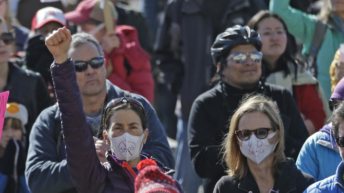 Utahns converge on the State Capitol to protest Wasatch Front air quality Saturday, Jan. 31, 2015, in Salt Lake City. People gathered on the Capitol steps, many wearing surgical and gas masks, others with placards on yardsticks to call on state lawmakers to do something to cut into the smog that blankets Utah's urban valleys in the winter. The state legislature plans to consider $28 million worth of proposals designed to improve air quality during the upcoming legislative session. (AP Photo/Rick Bowmer)