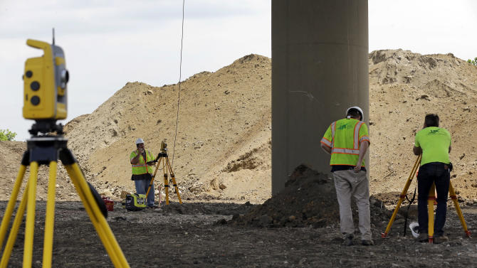 Surveyors stand near a tilting support column that is holding up the Interstate 495 bridge over the Christina River near Wilmington, Del., Tuesday, June 3, 2014, after it was closed due to the discovery of tilting support columns. The closure created heavier-than-normal traffic conditions for motorists on Interstate 95, a major East Coast artery. The bridge normally carries about 90,000 vehicles a day. (AP Photo/Patrick Semansky)