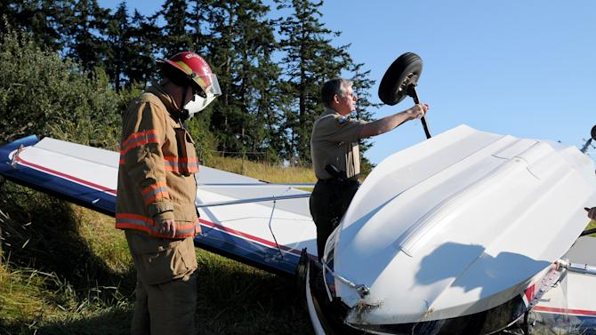 """In this Friday, Aug. 31, 2012 photo provided by the San Juan Islander, authorities examine a plane, piloted by author Richard Bach, that crashed in a field in Friday Harbor, Wash. Bach, the author of the 1970s best-selling novella """"Jonathan Livingston Seagull"""" among other spiritually oriented writings often rooted in themes of flight, was in serious condition Saturday at Harborview Medical Center. (AP Photo/San Juan Islander, Matt Pranger) MANDATORY CREDIT"""