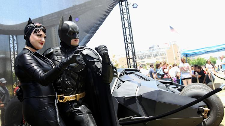 "Comic-Con attendees Katie Mitchell, left, and Jonathan Graves, from Los Angeles, strike a pose in front of the Tumbler Batmobile ""Batman Begins"" and ""The Dark Knight"" during Comic-Con, Saturday, July 14, 2012, in San Diego. (Photo by Matt Sayles/Invision/AP)"