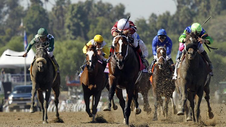 Tapizar, center, ridden by Corey Nakatani, crosses the finish line to win the Breeders' Cup Dirt Mile horse race, Saturday, Nov. 3, 2012, at Santa Anita Park in Arcadia, Calif.(AP Photo/Mark J. Terrill)