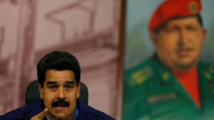 "Venezuela's President Nicolas Maduro speaks next to a painting of the late Hugo Chavez, during a news conference at Miraflores Presidential Palace in Caracas, Venezuela, Friday, Feb. 21, 2014. Speaking Friday to international media, Maduro called out what he said was a ""campaign of demonization to isolate the Bolivarian revolution."" (AP Photo/Fernando Llano)"