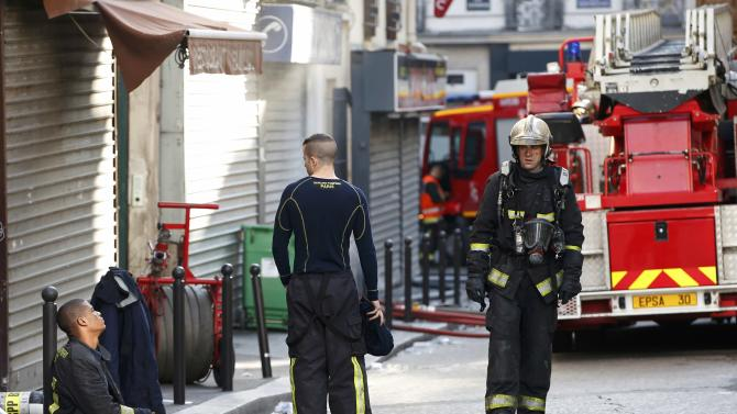 French firefighters of Paris Fire Brigade extinguish the fire that broke-out overnight in an apartment building in central Paris