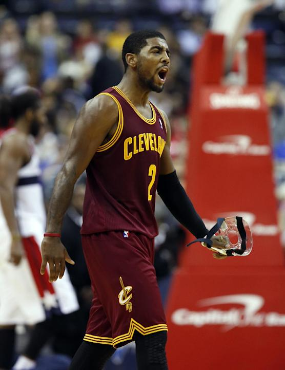 Cleveland Cavaliers guard Kyrie Irving (2) celebrates his shot during a timeout in overtime of an NBA basketball game against the Washington Wizards, Saturday, Nov. 16, 2013, in Washington. Irving had