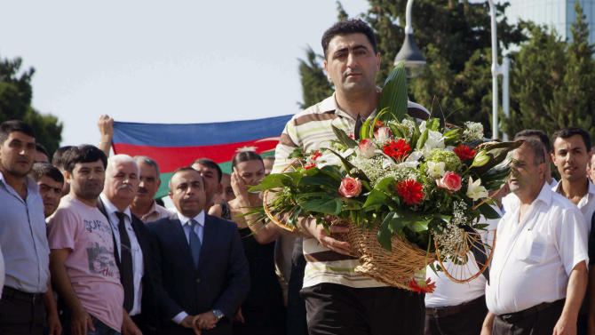 FILE - In this Aug. 31, 2012 file photo, Azerbaijani military officer Ramil Safarov lays flowers at Martyrs' Alley national memorial in the Azerbaijan's capital Baku. Safarov, sentenced to life in prison in Hungary for the murder of an Armenian man, was sent back to his homeland on Aug. 31 and, despite assurances, was immediately pardoned and freed by Azerbaijan's president. (AP Photo/Aziz Karimov, File)