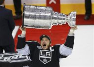 Los Angeles Kings' Dustin Brown holds up the Stanley Cup after his team defeated the New Jersey Devils in Game 6 of the NHL Stanley Cup hockey final in Los Angeles