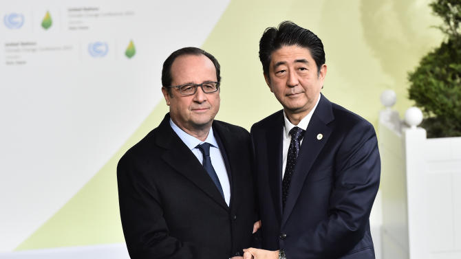 French President Francois Hollande, left, greets Japan's Prime Minister Shinzo Abe as he arrives for the COP21, United Nations Climate Change Conference, in Le Bourget, outside Paris, Monday, Nov. 30, 2015. (Loic Venance/Pool Photo via AP)