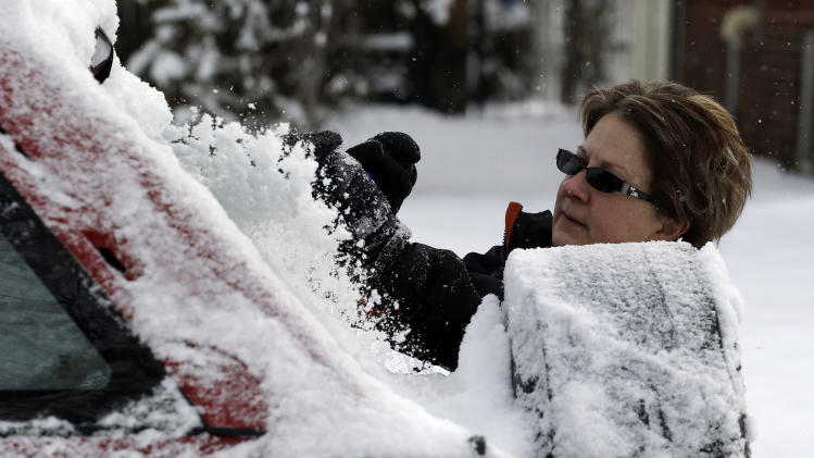 Kay Nelson scrapes ice and snow from her vehicle in Denver on Thursday, Feb. 21, 2013. A fast moving winter storm passed through Colorado Wednesday night and Thursday morning dropping as much as a foot of snow in areas of the state. (AP Photo/Ed Andrieski)