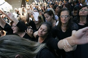 Women mourn, at the funeral of three Christian Syrians …