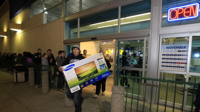 Christian Adorno, 13, walks out of a Best Buy with a 40-inch television Friday, Nov. 23, 2012, in Mayfield Heights, Ohio. The store opened at 12 a.m. on Friday. (AP Photo/Tony Dejak)