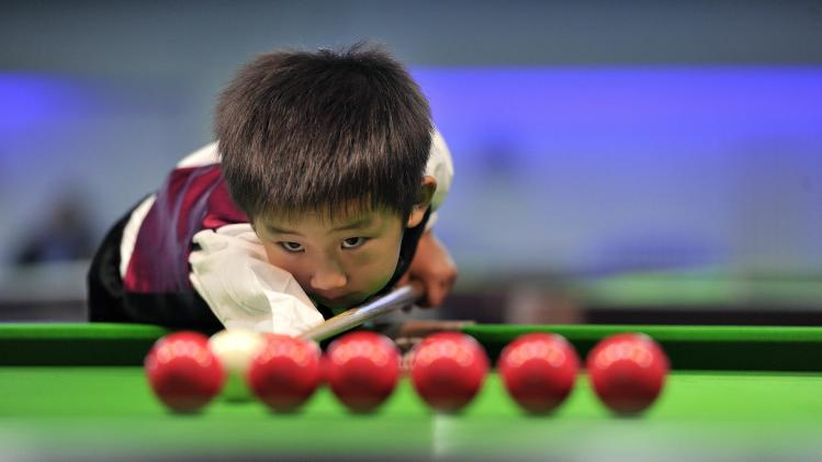 Three-year-old Wang practises before playing snooker with seven-time World Championship winner Hendry in Beijing