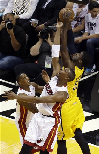Miami Heat center Chris Bosh (1) and guard Mario Chalmers (15) defend Indiana Pacers center Roy Hibbert (55) during the first half of Game 1 in their NBA basketball Eastern Conference finals playoff s