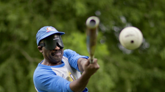 """Jimmie Burnette, who lost his vision to a brain tumor in 2010, practices batting during a blind baseball workout in Atlanta on July 13, 2013. """"Right now, I just try to take it day by day, one step at a time. BEEP baseball is helping me out. It takes away from me thinking about I'm less than a man, Now I realize I'm still the same man, just have to do things differently now,"""" he says. (AP Photo/David Goldman)"""