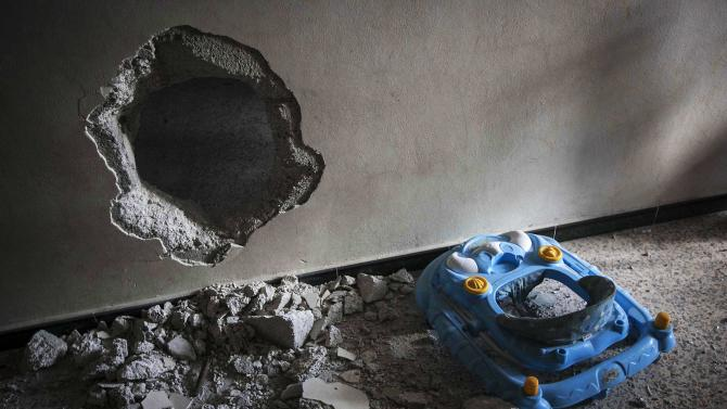 In this Wednesday, Dec. 5, 2012 photo, a baby walker is seen near a hole in a wall, recently done by Free Syrian Army fighters to help them during heavy clashes with government forces in Aleppo, Syria. (AP Photo/Narciso Contreras)