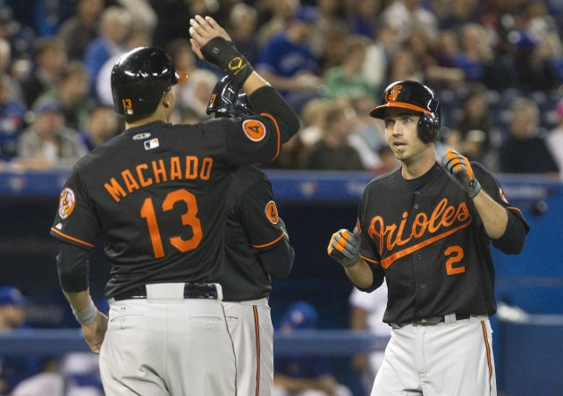 Baltimore Orioles Machado waits at home plate to congratulate teammate Hardy after he hit a three-run home run against the Toronto Blue Jays during their MLB American League baseball game in Toronto