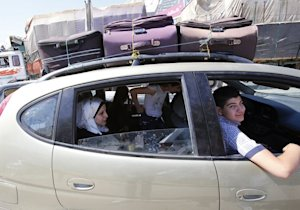 A family in their car loaded with suitcases as they…