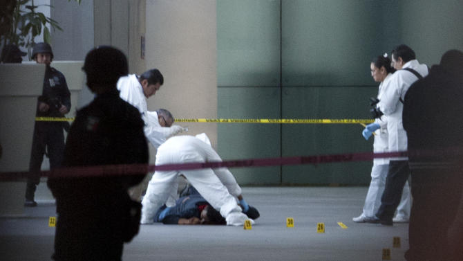 ADVANCED FOR USE SUNDAY FEB. 3 AND THEREAFTER FILE - In this Monday, June 25, 2012 file photo, a forensic team inspects a body at Mexico City's International Airport Terminal 2, . Men wearing what appeared to be police uniforms opened fire in a food court at Mexico City's international airport on Monday, killing three federal policemen on an anti-drug mission. The incident drew criticism of the U.S. western hemisphere anti-narcotics strategy that in Mexico, for example, has focused among other things, on improving the professionalism of the federal police but has backfired when foreign partners have proved too inexperienced to fight drug traffickers or so corrupt they switched sides. (AP Photo/Alexandre Meneghini, file)
