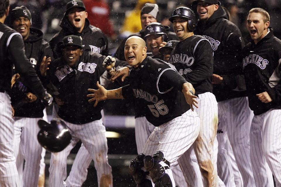 Colorado Rockies catcher Ramon Hernandez, front, joins teammates in welcoming to home plate Todd Helton after he hit a two-run, walkoff home run against the Arizona Diamondbacks in the ninth inning of the Rockies' 8-7 victory in a baseball game in Denver on Saturday, April 14, 2012. (AP Photo/David Zalubowski)
