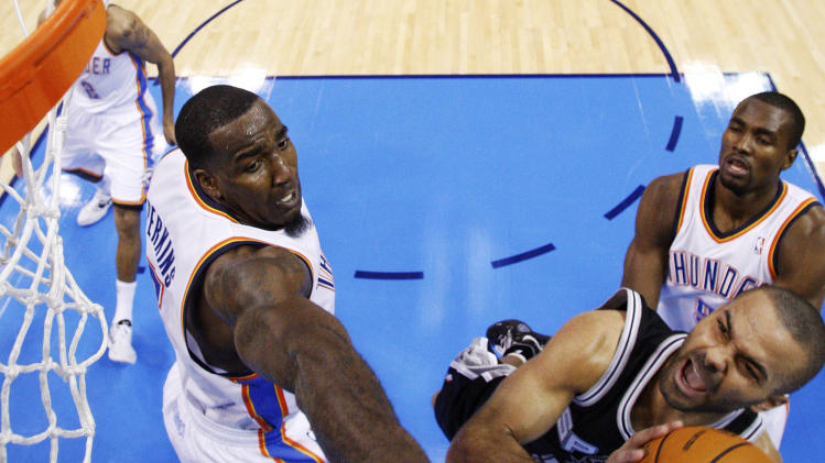 San Antonio Spurs guard Tony Parker, center, shoots between Oklahoma City Thunder center Kendrick Perkins, left, and forward Serge Ibaka, right, in the second quarter of an NBA basketball game in Oklahoma City, Sunday, Jan. 8, 2012. Oklahoma City won 108-96. (AP Photo/Sue Ogrocki)